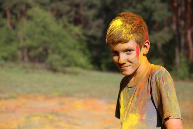 Nastoletni chłopak w holi maluje. portret chłopca na festiwalu kolorów holi