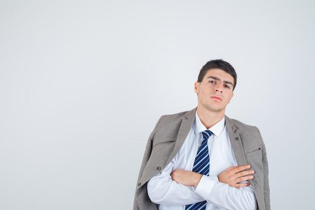 Nastoletni chłopak w koszuli, marynarce, krawacie w paski, stojący ze skrzyżowanymi rękami i wyglądający pewnie, widok z przodu.
