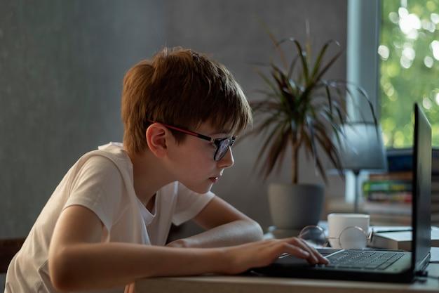 Nastoletni chłopak w okularach pracuje z laptopem. nauka na odległość. przygotowanie do egzaminów w szkole. gracz dziecięcy.