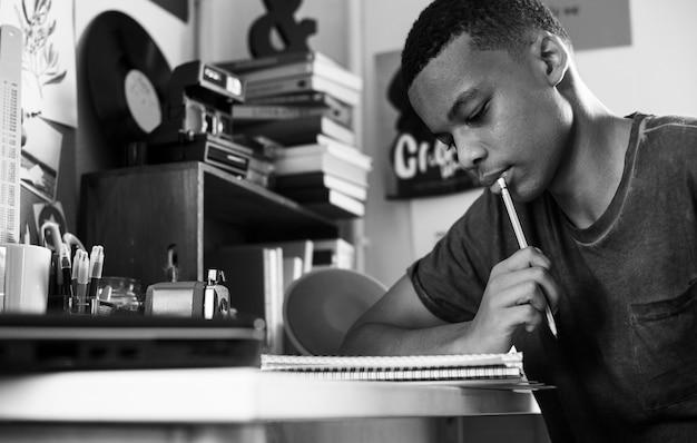 Nastoletni chłopak w sypialni robi pracy główkowaniu