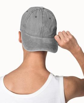 Nastoletni chłopak w szarej czapce szczery na sesję mody ulicznej