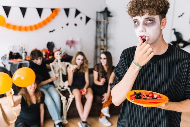 Nastoletni chłopak z kłami je cukierek na halloween przyjęciu