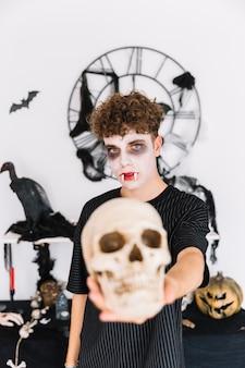 Nastoletni chłopak z kłami trzyma czaszkę