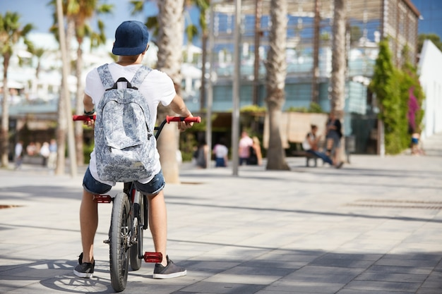 Nastoletni chłopak z plecakiem i czapkę na rowerze