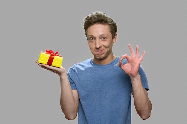 Nastoletni chłopak z pudełko pokazujący symbol ok. zdziwiony nastoletni facet trzyma pudełko i gestykuluje ok na szarym tle.