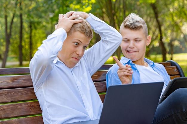 Nastoletni chłopcy na ławce w parku bawią się i relaksują