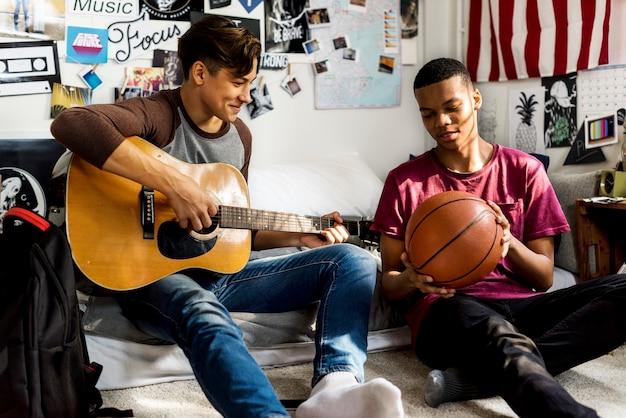 Nastoletni chłopcy wiszące w sypialni muzyka i sport koncepcja hobby