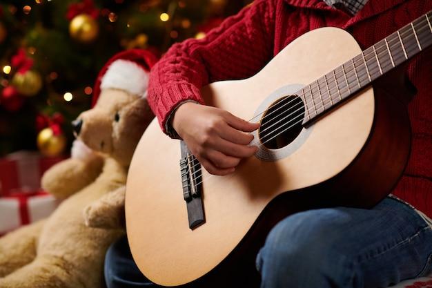 Nastoletni chłopiec grający na gitarze, siedzący pod domem w pobliżu ozdobionego choinki ze światłami, przebrany za pomocnika świętego mikołaja - wesołych świąt i wesołych świąt!