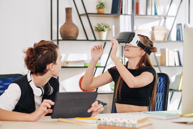 Nastoletni chłopiec i dziewczynka testują nową aplikację do stworzonego przez siebie zestawu słuchawkowego do wirtualnej rzeczywistości