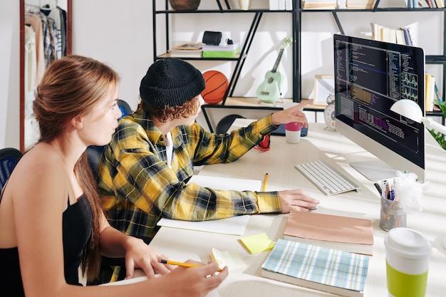 Nastoletni chłopiec i dziewczynka wspólnie pracują nad pracą domową na lekcjach informatyki i szukają błędów w kodzie programistycznym