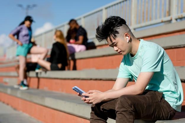Nastoletni chłopiec korzystający sam ze smartfona, z dala od przyjaciół