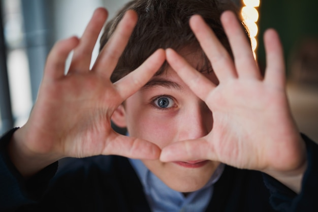 Nastoletni chłopiec o niebieskich oczach żartobliwie spogląda przez ramę z palców