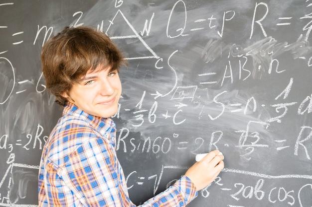Nastoletni chłopiec pisze kredą skomplikowane wzory matematyczne na czarnej tablicy