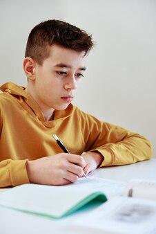 Nastoletni chłopiec pisze pracę domową w domu