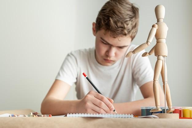 Nastoletni chłopiec rasy kaukaskiej uczy się rysować chłopiec rysuje mężczyznę na modelu kreatywnej lekcji rysowania hobby