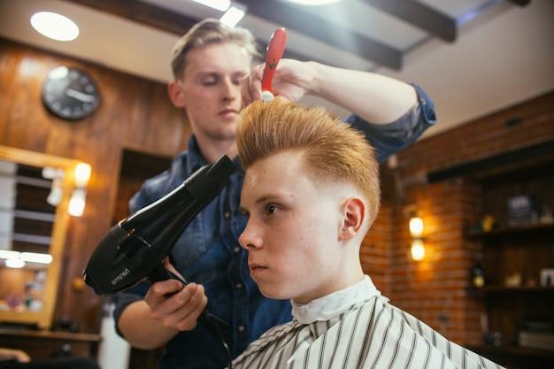 Nastoletni chłopiec rudy fryzury fryzjer w sklepie fryzjerskim. modna stylowa fryzura retro. portret dziecka z piękną fryzurą. rosja, swierdłowsk, 12 lutego 2019 r.