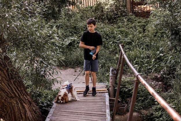 Nastoletni chłopiec spaceruje z psem po moście na wsi