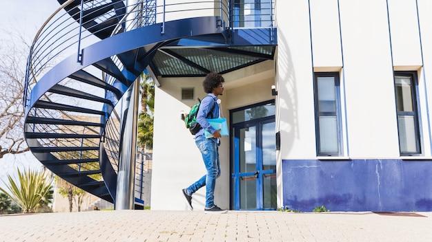Nastoletni chłopiec trzyma książkę w ręku spaceru przed budynkiem uniwersytetu