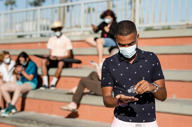 Nastoletni chłopiec używający środka dezynfekującego do rąk na zewnątrz w nowej normie