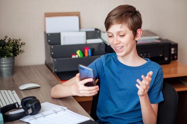 Nastoletni chłopiec wykonuje rozmowę wideo, używając swojego telefonu komórkowego do swoich przyjaciół, kolegów z klasy i krewnych.