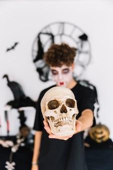Nastoletni chłopiec z halloweenową zombie ponurą mienie czaszką