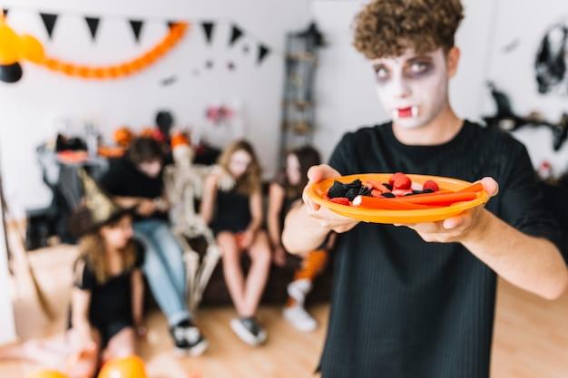 Nastoletni chłopiec z kędzierzawym włosy i wampira ponurą daje talerza z marmoladą