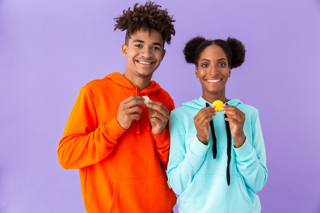 Nastoletni facet i dziewczyna trzyma ciastka makaronik, odizolowane na fioletowej ścianie