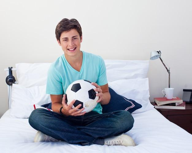 Nastoletni facet trzyma piłki nożnej piłkę