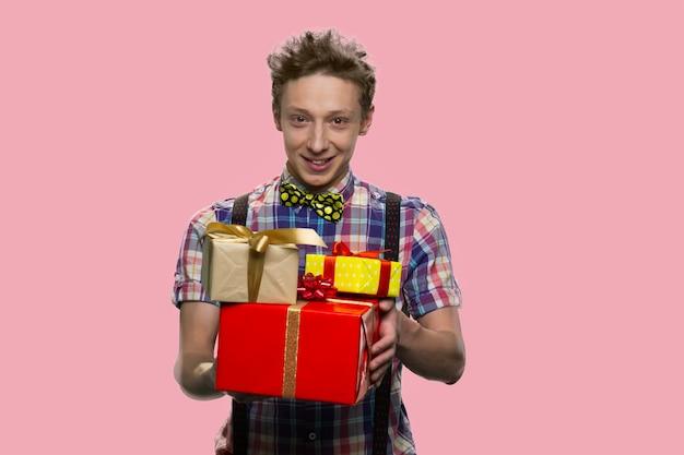 Nastoletni facet z muszką trzyma stos prezentów. szczęśliwy chłopiec w szelkach na białym tle na różowym tle.
