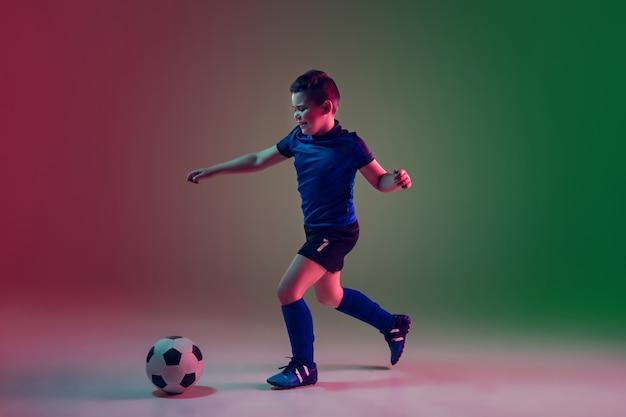 Nastoletni mężczyzna piłkarz lub piłkarz, chłopiec na gradiencie w świetle neonowym