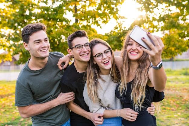 Nastoletni przyjaciele przy parkiem bierze selfie i ma zabawę