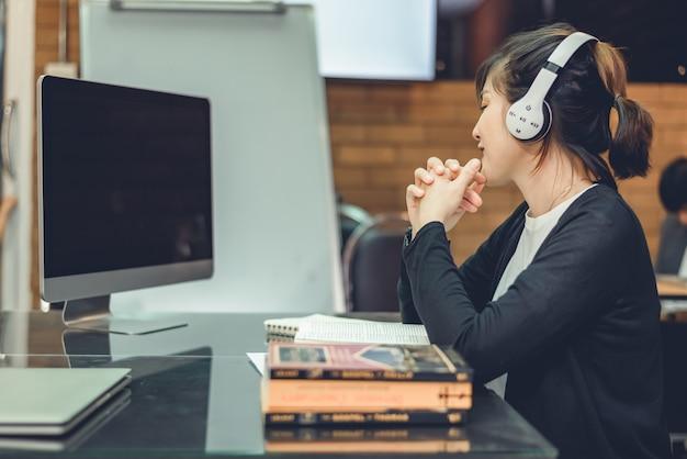 Nastoletni student z azji nosi bezprzewodowe słuchawki do słuchania muzyki i radośnie się relaksuje podczas lekcji online. studenci patrzący na komputery uczący się online