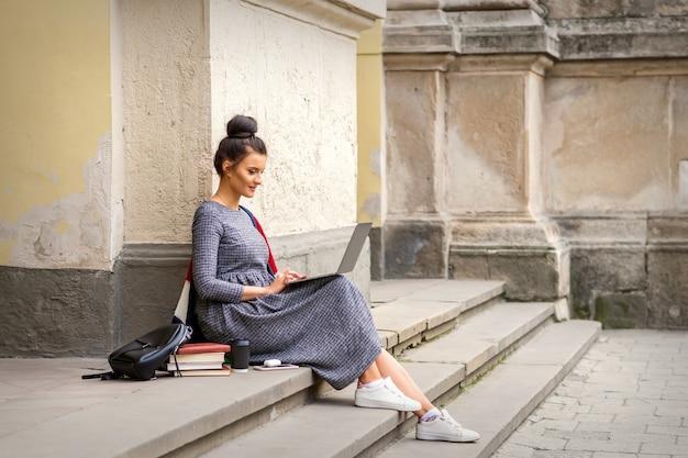 Nastoletni szczęśliwy student pracuje na komputerze przenośnym na schodach na zewnątrz