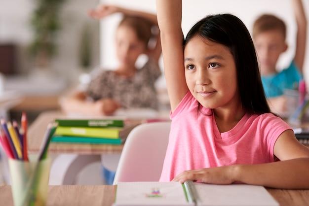 Nastoletni uczeń podnosząc rękę w klasie