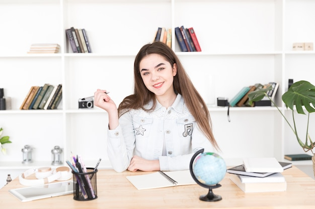 Nastoletni uczeń siedzi przy stole z piórem w rękach