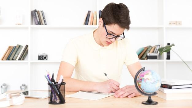 Nastoletni uczeń siedzi przy stołem i pisze w szkłach