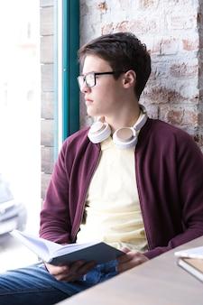 Nastoletni uczeń w szkłach i hełmofonach siedzi przy stołem blisko okno