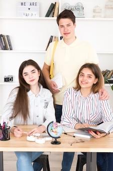 Nastoletni ucznie studiuje przy stołem i patrzeje kamerę