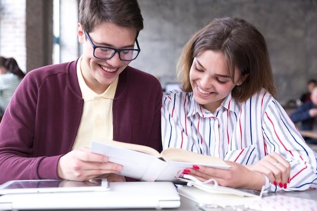 Nastoletni ucznie uśmiecha się i czyta książki przy stołem