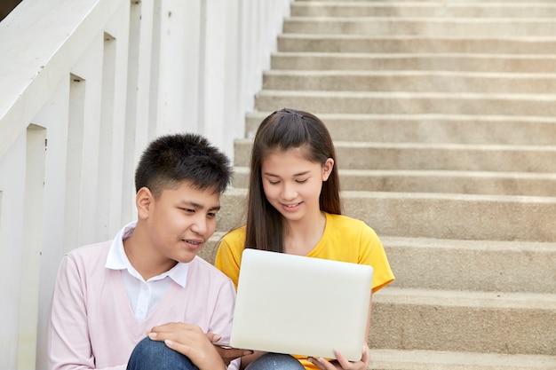 Nastoletni uczniowie pracują w szkole na laptopie