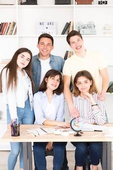 Nastoletni uczniowie zebrali się przy stole w klasie