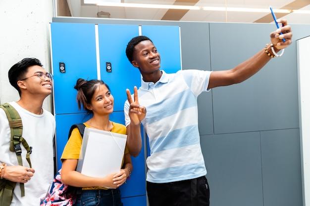 Nastoletni wielorasowi koledzy z klasy robią sobie selfie na szkolnym korytarzu skopiuj przestrzeń powrót do szkoły