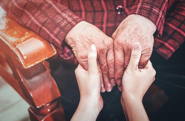 Nastoletnia azjatycka opiekunka młodej dziewczyny trzymająca babcię za ręce, koncepcja pomocy w opiece nad osobami starszymi z ciemnym tłem, zbliżenie, kopia przestrzeń, przycięty widok