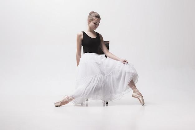 Nastoletnia balerina w białej spódnicie pozuje na krześle