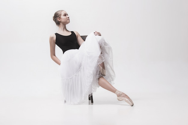 Nastoletnia baletnica w białym opakowaniu siedzi na krześle