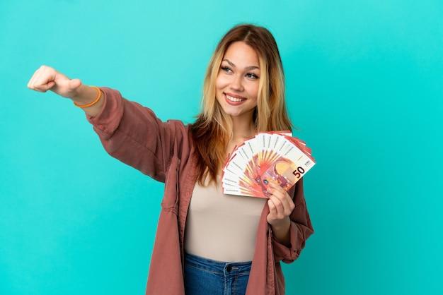Nastoletnia blondynka bierze dużo euro na odosobnionym niebieskim tle, pokazując gest kciuka w górę