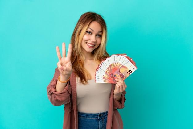 Nastoletnia blondynka bierze dużo euro na odosobnionym niebieskim tle szczęśliwa i liczy trzy palcami