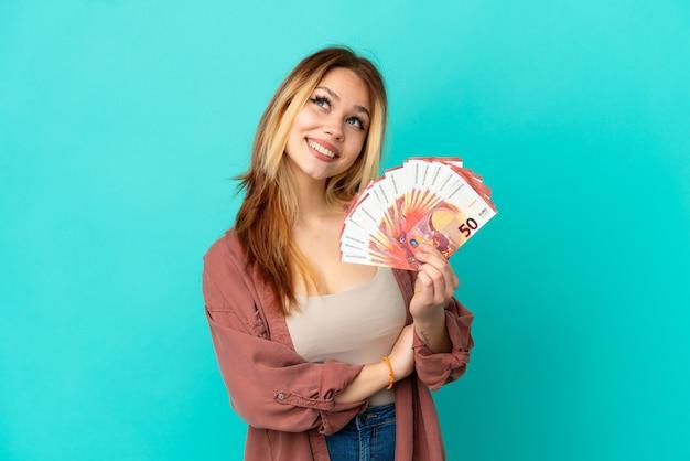 Nastoletnia blondynka bierze dużo euro na pojedyncze niebieskie tło, patrząc w górę, uśmiechając się