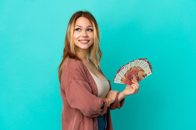 Nastoletnia blondynka bierze dużo euro na pojedyncze niebieskie tło z rękami skrzyżowanymi i szczęśliwa