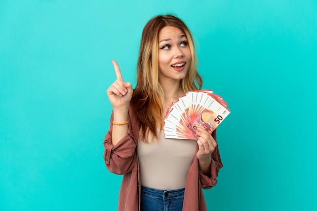 Nastoletnia blondynka bierze dużo euro nad odosobnioną niebieską ścianą, zamierzając zrealizować rozwiązanie, podnosząc palec w górę